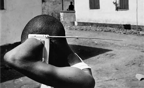 Muž s useknutými končetinami poslouchá rádio v táboře pro oběti občanské války ve Freetownu v Sierra Leone. (listopad 2005)