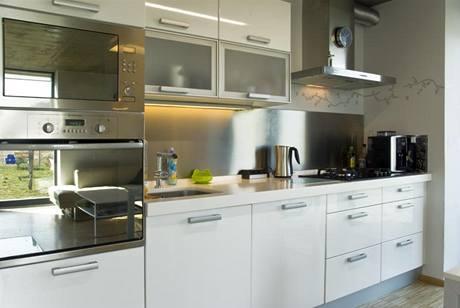 Masivní pracovní deska z kompozitního materiálu a hladké obložení stěny nerezovým plechem usnadňují údržbu