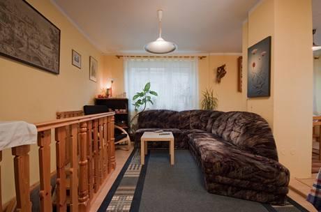 Obývací pokoj před proměnou, část prostoru zabírá schodiště