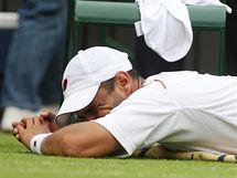 Alejandro Falla se nechává ošetřovat během zápasu s Rogerem Federerem ve Wimbledonu.