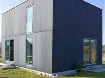 Obklad cembonitovými deskami, okna rozmístěná v rámci rastru obkladu a osazená v líci fasády, to jsou prostředky, kterými architekti udrželi jednolitý kompaktní vzhled.