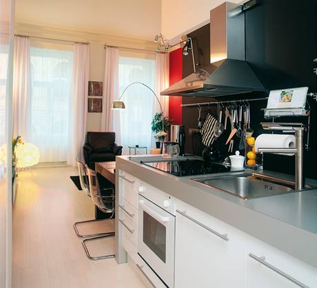Z obýváku se vstupuje do kuchyňky, z níž ve stejné linii, jako je kuchyňská sestava, vybíhá do obývacího pokoje jídelní stůl