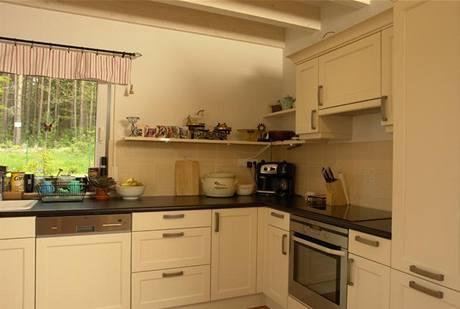 Bíle lakovaná kuchyňská linka s masivními úchytkami je moderní variací na kuchyňský nábytek dřívějších dob s rámovými dvířky a propracovanými detaily