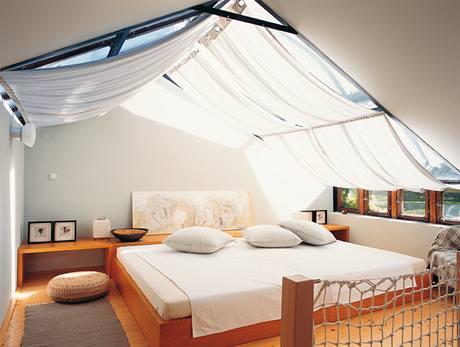 Hostinský pokoj s impozantní postelí, nad níž se vyjímá lněný zastiňovací závěs