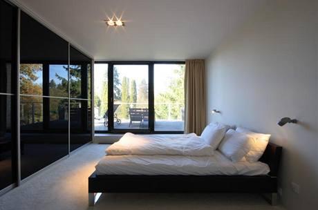 Jedinou ozdobou zcela účelně vybavené ložnice je výhled do lesa, který se objevuje nejen v okně, ale také se zrcadlí na prosklených dveřích skříňové stěny