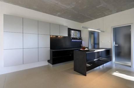 Kuchyňská linka má pracovní desku, obložení stěny a bočnice z tmavé žuly