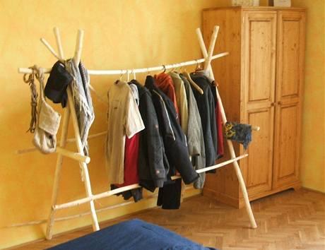 Stojan na oblečení je vyrobený z větví zbavených kůry a stažený páskou