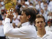 Rafael Nadal s trofejí pro vítěze Wimbledonu, v pozadí Tomáš Berdych