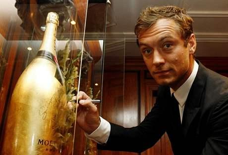 Americký herec Jude Law podepisuje zlatou lahev pro Centrum Paraple