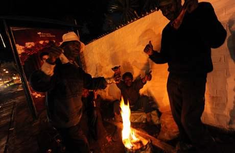 Bezdomovci v Johannesburgu se hřejí u zapáleného ohně.