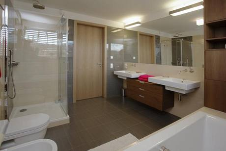 Do koupelny, vybavené elegantní italskou sanitární keramikou, navrhli sestavu skříněk s teakovou dýhou