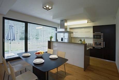 Kuchyň je otevřená do obývacího pokoje. Výtvarný efekt spočívá v kontrastu hladkých povrchů - dýhy wengé a bílého laku ve vysokém lesku, pracovní deska je vyrobena z kompozitního materiálu Technistone.