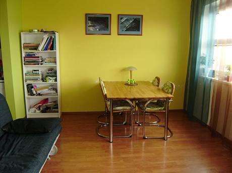 Stěna za jídelním stolem je žlutá, obrázky jsou z kalendáře