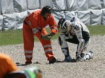 Český jezdec Jakub Smrž se za pomoci pořadatele zvedá ze země po pádu v závodě na Masarykově okruhu.