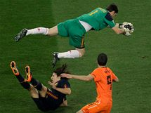 Iker Casillas placht� vzduchem nad le��c�m Carlesem Puyolem. P�ihl�� Robin van Persie.