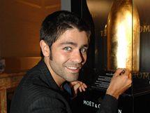 Herec Adrian Grenier podepisuje zlatou lahev pro Centrum Paraple