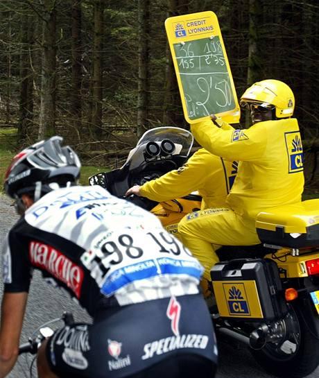 Michel Bationo z Burkiny Faso ukazoval cyklistům v úniku na Tour de France, jaký náskok mají před svými pronásledovateli.