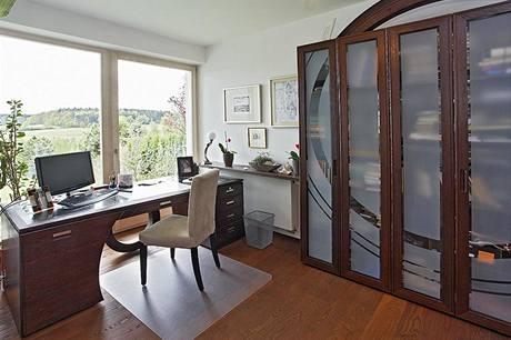 Do své pracovny si pán domu sám navrhl knihovnu i psací stůl. Opakující se kruhové motivy navozují  pocit propojení a harmonie.