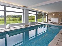 """Kamenná dlažba se """"přelévá"""" z prostoru bazénu až za prosklenou stěnu a v jemné vlně se mění v dřevěnou podlahu"""
