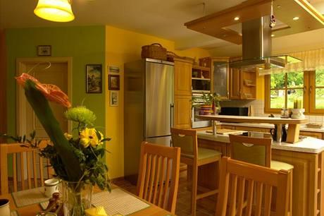Barové sezení u varné desky pro nedočkavé strávníky kuchyni i opticky odděluje od jídelní části