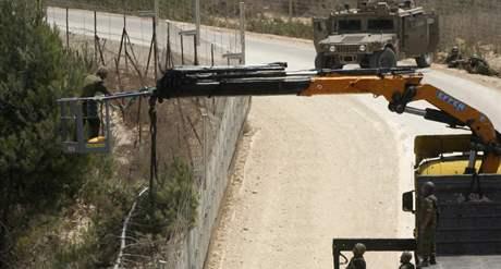Izraelští vojáci kácí strom na libanonské straně hranice. Jejich akce spustila přestřelku, při které zahynulo pět lidí