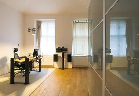 Vybavení pracovny tvoří bytelný kovový pracovní stůl, který vyrobil sám majitel bytu, a vestavné skříně