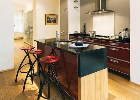 Kuchyňská sestava a barový pult mají vysoce leštěný povrch, který vytváří zajímavou kombinaci s úchytkami a hranami z hliníku