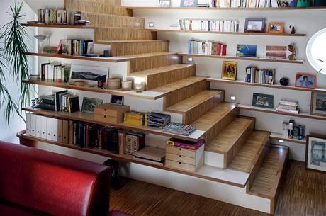 Podle architekta Tomáše Klance se využilo široké schodiště k odkládání menších předmětů, na boční straně jsou police, které opticky splývají s knihovnou