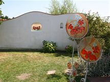 Malebná zídka s venkovským motivem zepečeným ve skle, další skleněné artefakty jsou rozmístěné po celé zahradě