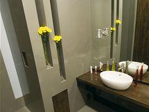 Koupelna s keramickým umyvadlem. Součástí koupelny jsou funkční, ale i dekorativní niky.