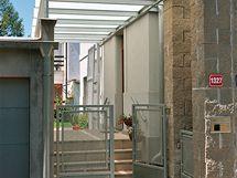 Ocelová konstrukce s kaleným sklem zastřešuje vstup již od branky a zároveň začleňuje garáž do celkového konceptu