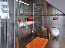 Oranžové doplňky zvýrazňují šedo-hnědou barevnost obkladů