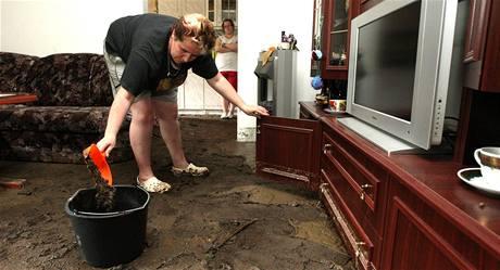 MIchaela Nováková z Janské uklízí bahno v obývacím pokoji po bleskové povodni v červnu 2010.