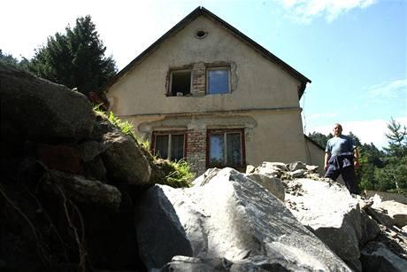 František Levý z Janské u svého domu - podemletý roh je zasypán kamením.