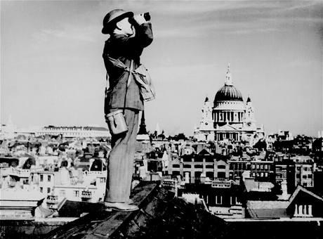 Britský voják vyhlíží německé bombardéry na střeše budovy v Londýně. V pozadí je vidět katedrála svatého Pavla. (září 1940)