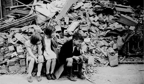 Děti z východního předměstí Londýna sedí u vybombardovaných trosek domu, kde předtím bydleli. (1940)