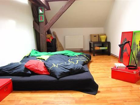 V malé ložnici spí mladý pár na matraci. Noční stolky nahradily papírové krabice