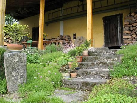 Na zahradu vede pět schodů z pískovce. Jejich okraje lemují převážně skalničky