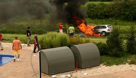 Zaměstnanci z prodejny bazénů se pokoušejí uhasit hořící BMW