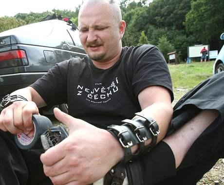 Petr Fiedor si obmotává speciální boty se střepy, aby vyšlápl na horu Říp