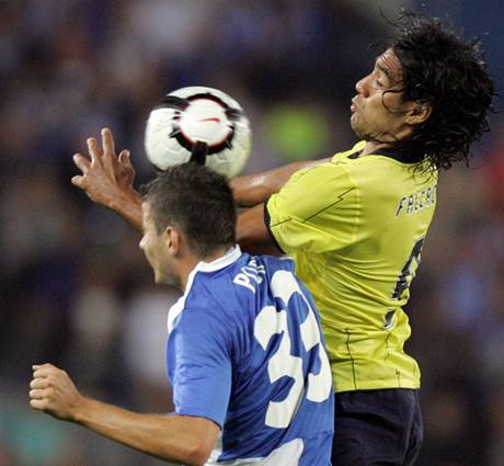 Záložník blgického Genku Daniel Pudil (vlevo) hlavičkuje, ačkoliv výš vyskočil Zanate Falcao z FC Porto.