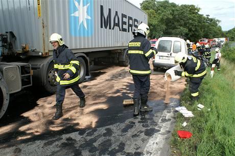 Hasiči zasypávají pohonné hmoty, které vytekly při tragické nehodě u Ješína na Kladensku.