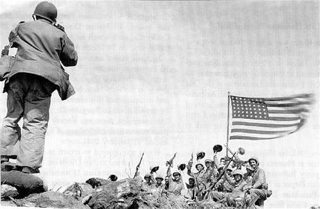 Fotograf Joe Rosenthal pořizuje snímek radujících se amerických vojáků na vrcholu Mt. Suribachi. (23. února 1945)