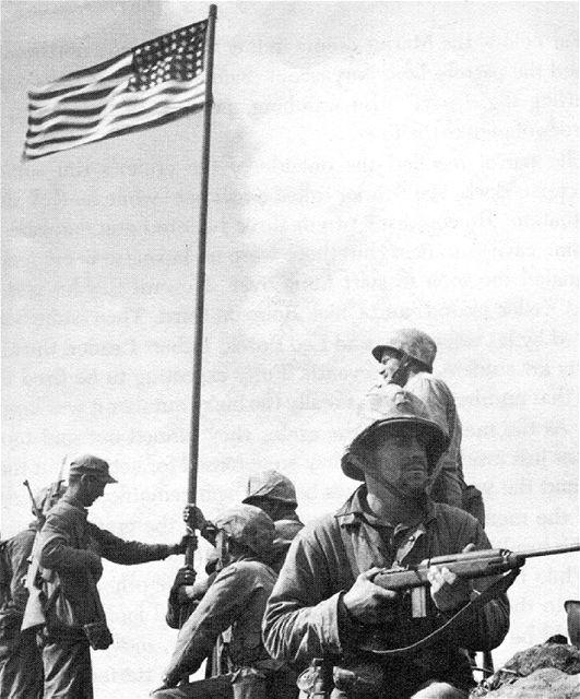 Vztyčování první americké vlajky na vrcholu Mt. Suribachi. (23. února 1945)