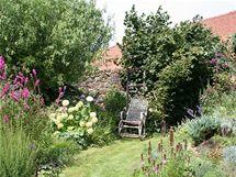 """""""Babiččina"""" romantická zahrada plná květin, vpravo vedle houpacího křesílka vstup do užitkové části zahrady"""