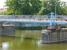 Zchátralý Tyršův most či spíše lávka využívá původních pilířů. Na místě stojí od roku 1964.