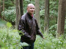 Kronikář Hostinného Tomáš Anděl v lese ukazuje na místo, kde by údajně mělo být pohřbeno několik desítek německých vojáků, zastřelených v červnu 1945.