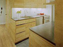 Kuchyně působí velmi prostorně. Jednoduché členění desky a kombinace dřeva s nerezem nezatěžují prostor