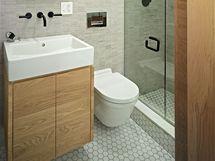 Minimalistická koupelna se sprchovým koutem je obložená italskou keramikou, která imituje přírodní kámen