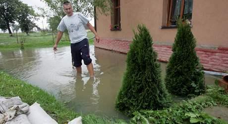 Edvard Kornas se snaží zabránit vodě, aby pronikla do jeho domu v Petrovicích u Karviné.